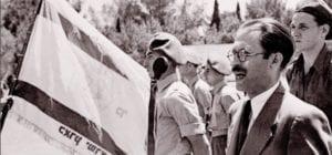 Menachem Begin (v pozadí vlajka Irgunu)