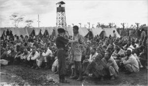 """Britský koncentrační tábor během protikoloniálního povstání Mau Mau v Keni. """"Práce a svoboda"""""""